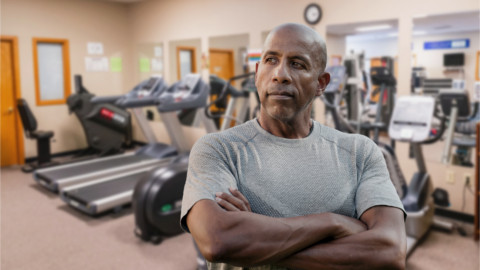 Fit African American man with Pacific Rehabilitation Centers therapy gym in background